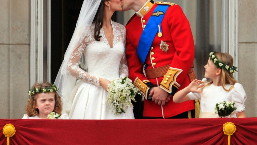 Britain's Prince William kisses his wife Kate, Duchess of Cambridge on the balcony of Buckingham Palace after the Royal Wedding in London Friday, April, 29, 2011.
