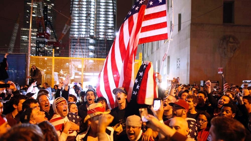 With the new One World Trade Center building in the background, second left, a large, jubilant crowd reacts to the news of Osama bin Laden's death at the corner of Church and Vesey Streets, adjacent to ground zero, during the early morning hours of Tuesday, May 2, 2011 in New York. (AP Photo/Jason DeCrow)
