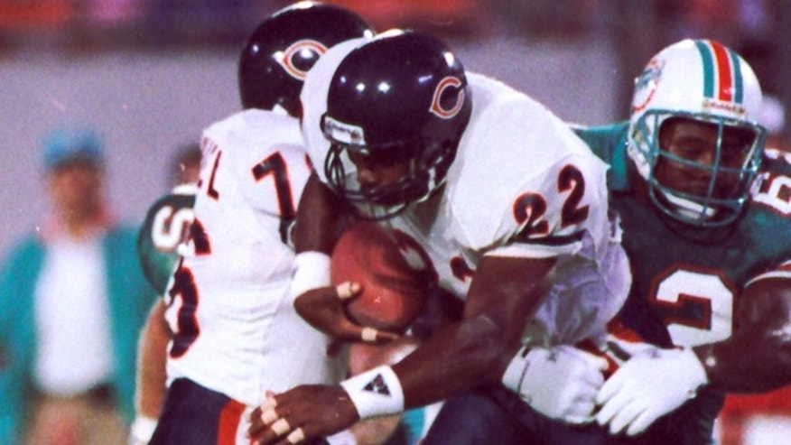 In this Aug. 14, 1989, file photo, Chicago Bears safety Dave Duerson (22) scrambles for running room after intercepting a pass as Miami Dolphins Jeff Uhlenhake (63) grabs hold during an NFL football game in Miami.