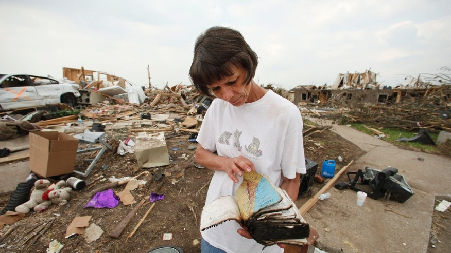 May 28: Bonnie Branham looks through a water-soaked Bible as she salvages belongings from her son's devastated apartment in Joplin, Mo.
