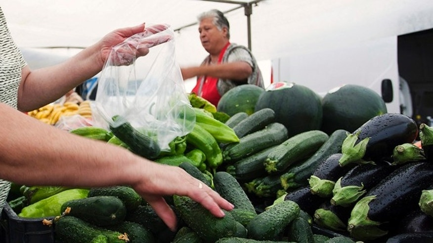 A woman buys cucumbers at a market in El Alquian, Almeria, in southeastern Spain, May 29, 2011.
