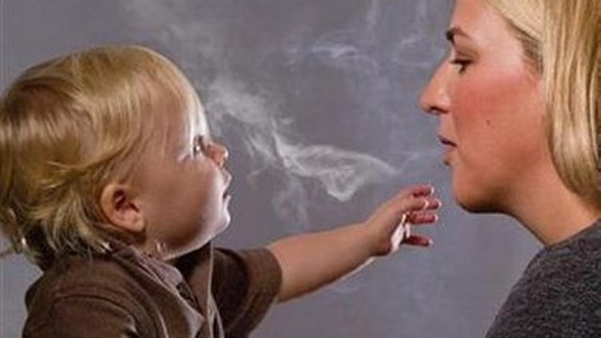 "This handout image, released on November 10, 2010 depicts a mother blowing cigarette smoke in a child's face in one of the Federal Drug Administration's proposed new ""graphic health warnings."""