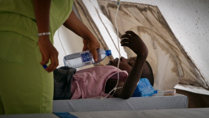 A woman gives water to her child as he receives treatment for cholera at a Doctors Without Borders, MSF, cholera clinic in Port-au-Prince.