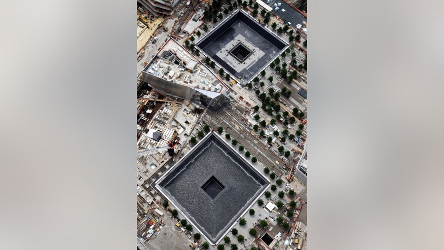 The memorial pools of the National September 11 Memorial and Museum are seen in this overhead view, Monday, June 20, 2011 at the World Trade Center site in New York. September will mark the tenth anniversary of the attacks of Sept 11, 2001. The pools are located where the twin towers once stood. (AP Photo/Mark Lennihan)