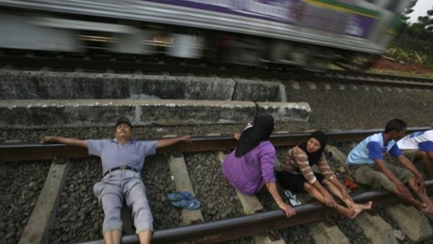 In this July 26, 2011 photo, villagers lie on a railway track for an electricity therapy in Rawa Buaya, Jakarta, Indonesia. People in the outskirt of the capital have been participating in the treatment believing that the the electricity current from the track could cure various diseases.