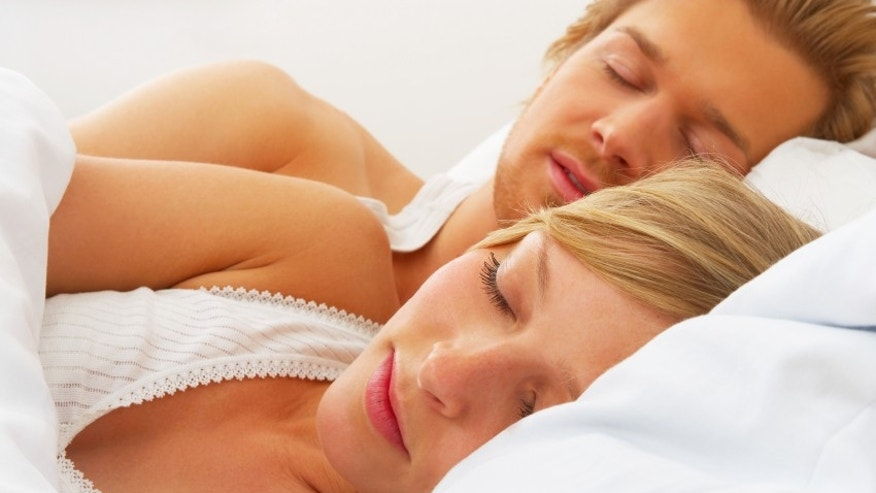 Young couple sleeping together in bed. A sensual and cute couple.