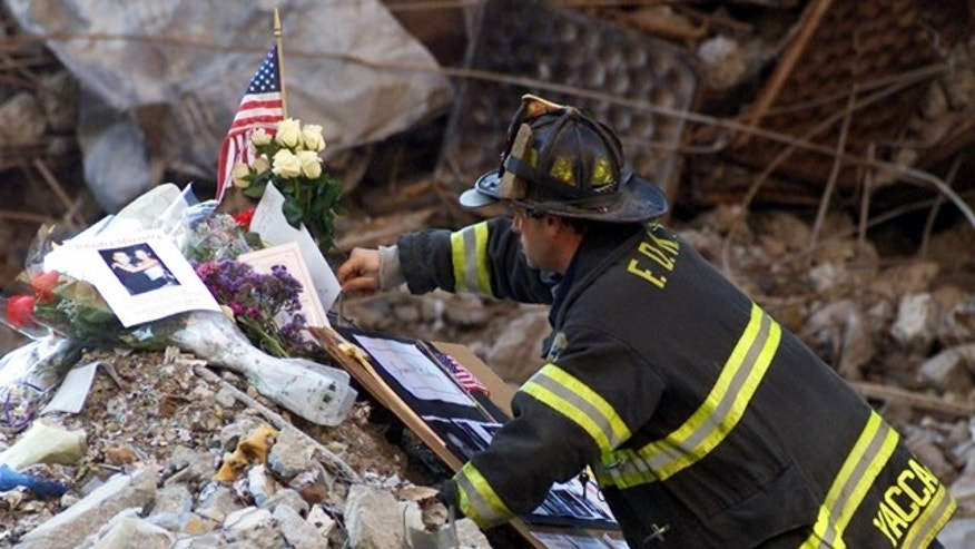 A New York City firefighter places flowers and mementos from familymembers of the victims of the World Trade Center disaster amidst thewreckage following a memorial service for the victims of the September11 attack at the site in New York, October 28, 2001. REUTERS/MikeSegarMS