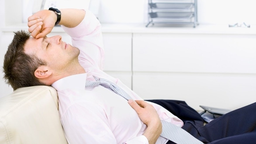 Mid-adult businessman lying on sofa at office, looking tired, eyes closed. Bright background.