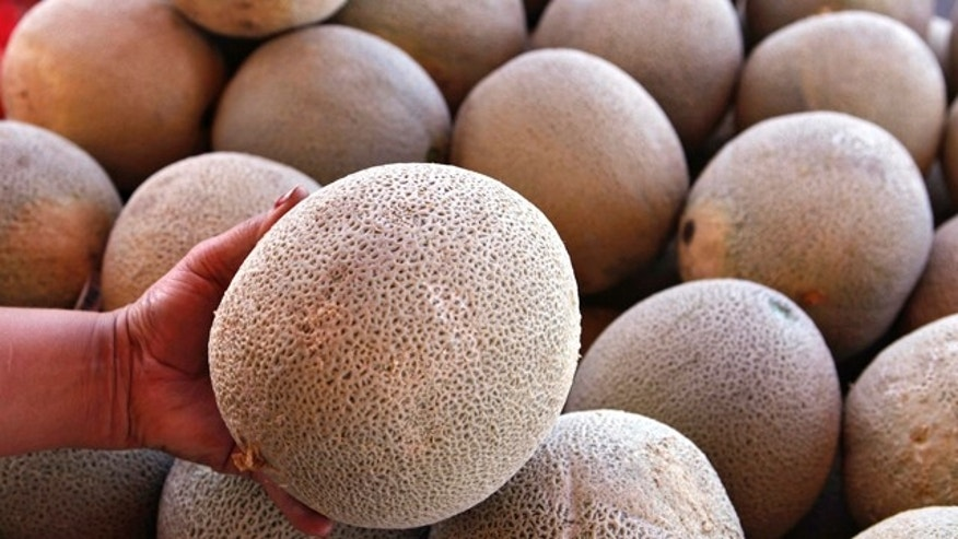 An operator of a fruit and vegetable stand near Denver holds a California-grown cantaloupe for sale at her business on Friday, Sept. 16, 2011. Federal and state officials have isolated a deadly outbreak of listeria to one cantaloupe farm near Holly, Colo. They have ordered a recall of 300,000 cases of melons grown on the Jensen Farms. Only California-grown cantaloupe could be found in Denver markets. (AP Photo/Ed Andrieski)