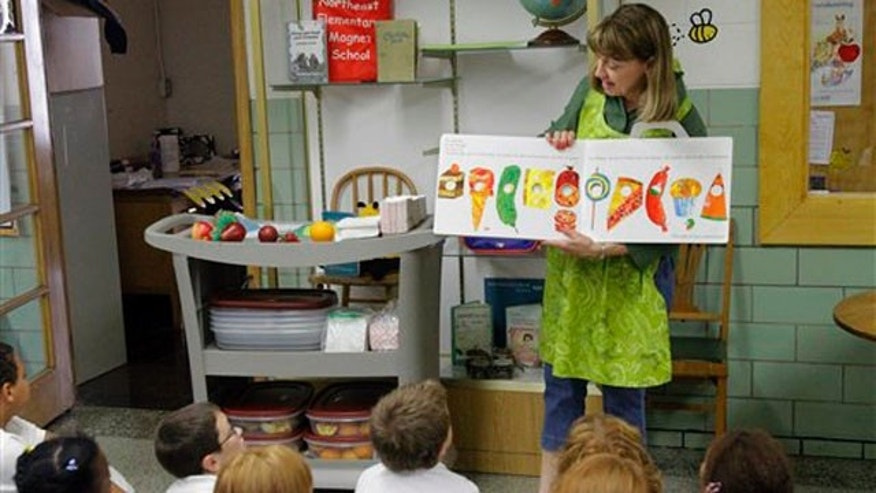 In this Sept. 20, 2011 photo, Nancy Henderson, home economic coordinator for the fresh fruit and vegetables program, works with the students at Northeast Elementary Magnet, in Danville, Ill.