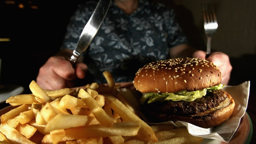 GLASGOW, UNITED KINGDOM - JUNE 07:  In this photo illustration a man eats a hamburger ind chips in a cafe on June 7,2006 in Glasgow, Scotland. New figures are suggesting that a large proportion of the population is clinically obese.  (Photo Illustration by Jeff J Mitchell/Getty Images)