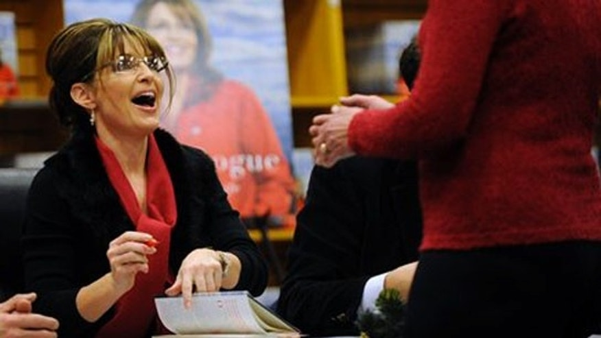 "Sarah Palin signs copies of her book ""Going Rogue"" at a book signing in Colorado Springs, Colo., on Tuesday, Dec. 8, 2009."