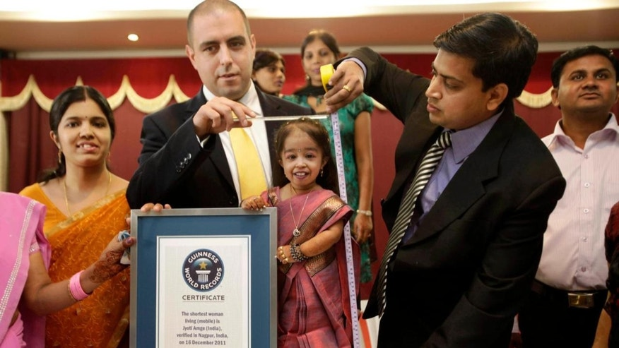"Guinness World Records adjudicator Rob Molloy, center, and Dr. Manoj Pahukar of Wockhardt hospital, right, measures Jyoti Amge in Nagpur, India, Friday, Dec. 16, 2011. Amge, 18, is now eligible under the Guinness World Record guidelines for the ""Shortest Woman in the world"" title measuring 2 feet. (AP Photo/Manish Swarup)"