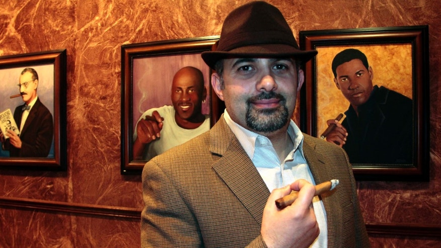 Ismail Houmani, founder and director of La Casa De La Habana, enjoys a cigar at his establishment on Wednesday, Dec. 22, 2010 in Detroit. Cuba's government-controlled tobacco company is suing the owner of cigar shops in the Detroit area, claiming his business' name is too similar to its own global franchise. Houmani owns four cigar lounges called La Casa De La Habana, in Detroit, Plymouth, Mich., Ann Arbor, Mich., and Toledo, Ohio. Cubatabaco's stores are named La Casa del Habano. Cuba can't do business in America because of a nearly 50-year-old trade embargo. Nonetheless, Cubatabaco claims it still has a right to protect its U.S. trademark.  (AP Photo/Jerry S. Mendoza)
