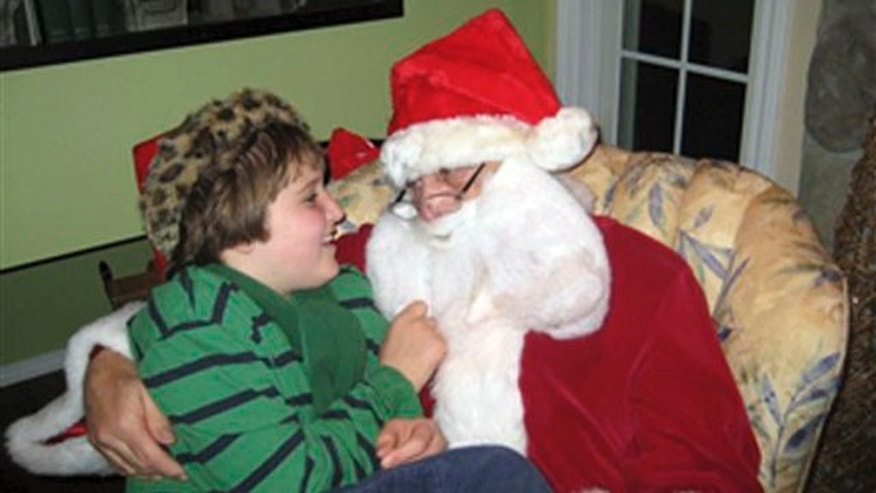 "This Dec. 11, 2011 photo provided by Darlene Borre, shows her son, Ben Borre, 10, of West Hartford, Conn., with an autism-friendly Santa Claus, Ray Lepak of Manchester, Conn., who is also Ben's grandfather. For families of many children on the autism spectrum, a visit with Santa Claus at Christmas can be nearly impossible --unless they're visiting one of the growing number of ""sensitive"" Santas."