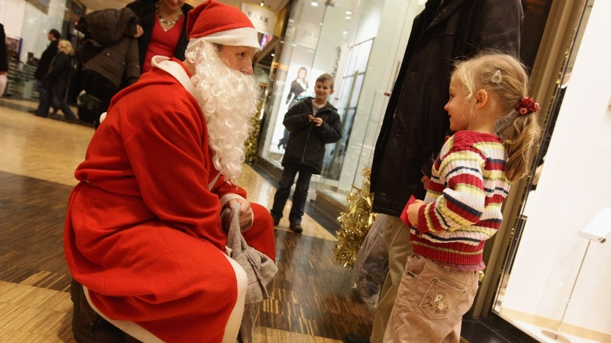BERLIN - DECEMBER 05:  A man dressed as Santa Claus offer sweets to children at the Alexa shopping mall on December 5, 2009 in Berlin, Germany. Retailers are hoping for a strong Christmas season to help make up for a difficult financial year.  (Photo by Sean Gallup/Getty Images)