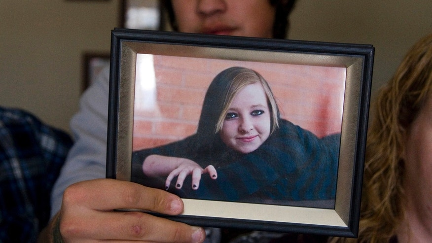 In this Dec. 6, 2011 photo, Nathan Wittman, 19, holds a photo of Jenni Lake, who died of cancer shortly after giving birth to their son, Chad Michael Lake Wittman.