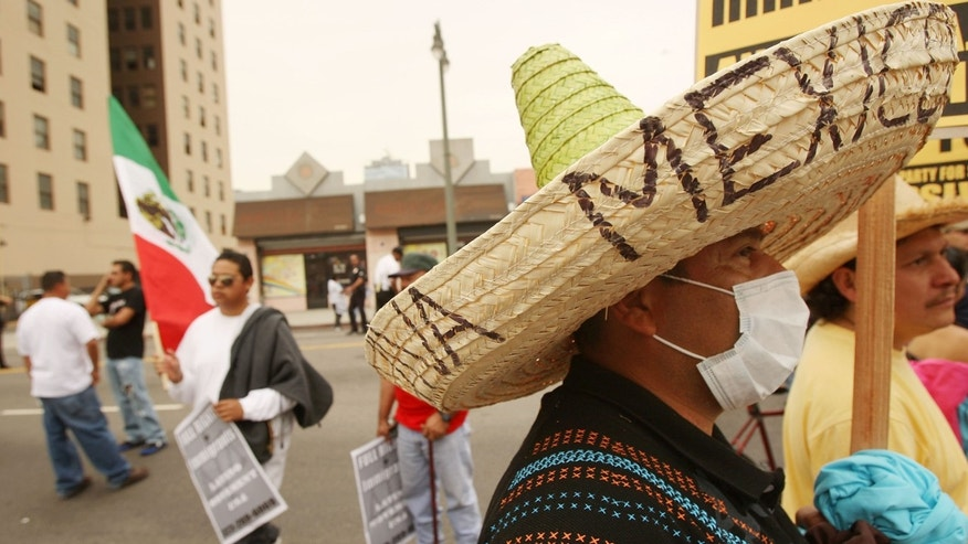 LOS ANGELES, CA - MAY 01:  Trujillo Guiermo wears a mask for protection against exposure to the swine flu virus, H1-N1, and a man carries a Mexican flag as demonstrators rally for immigrant worker rights on May Day, May 1, 2009 in Los Angeles, California. Thousands of people are participating in seven May Day immigrant rights protest marches throughout the Los Angeles area. At the 2007 May Day marches, demonstrators and bystanders were beaten by Los Angeles police officers at MacArthur Park, resulting in a $12.85 million payout by the city to settle nine lawsuits. In a breakdown of political unity, activists groups are holding marches independently of one another this year.  (Photo by David McNew/Getty Images)