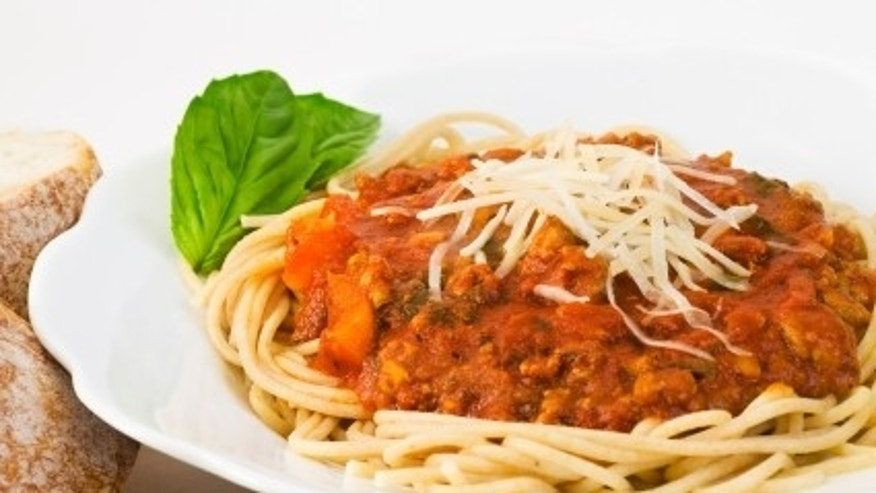 Bowl of whole wheat spaghetti and sauce. The sauce includes ground turkey, fresh basil, tomato sauce, bell peppers, onions, mushrooms, garlic, olive oil and italian seasonings.