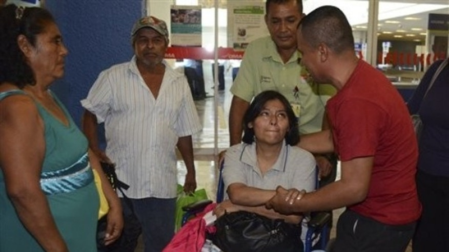 April 16: Norma Ramirez, center in wheelchair, is welcomed by her ex-husband, Diogenes Rodriguez, right, at the airport in Acapulco, Mexico.  (AP Photo/Bernandino Hernandez)