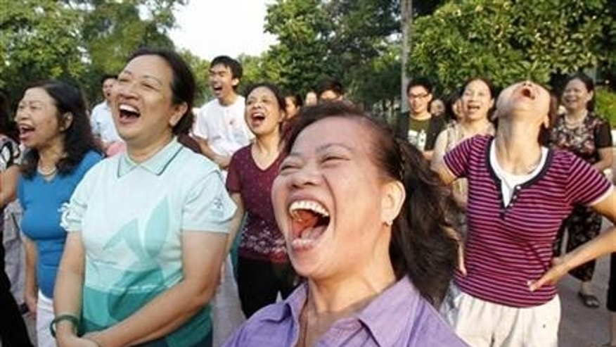 Members of the Laughter Yoga club practise laughing during morning exercise at a public park in Hanoi September 24, 2011. REUTERS/Kham