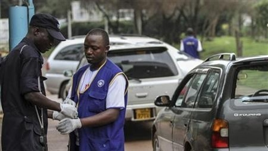 Security personnel wear gloves to check motorists entering and exiting Mulago hospital in Uganda&#39&#x3b;s capital of Kampala July 31, 2012. REUTERS/Edward Echwalu