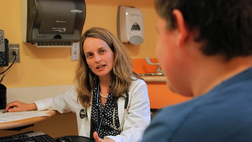 Dr. Sarah de Ferranti, director of preventive cardiology at Boston Children's Hospital, left, meets with patient Quinn Voccio, 14, right, in Waltham, Mass. (AP Photo/Steven Senne)