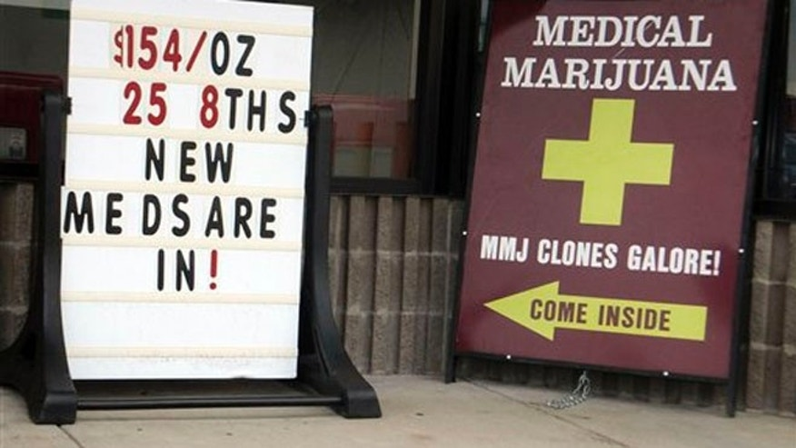 "Sidewalk ads outside a west Denver medical marijuana dispensary advertise low prices and ""Clones Galore!"" on Monday, Aug. 13, 2012."