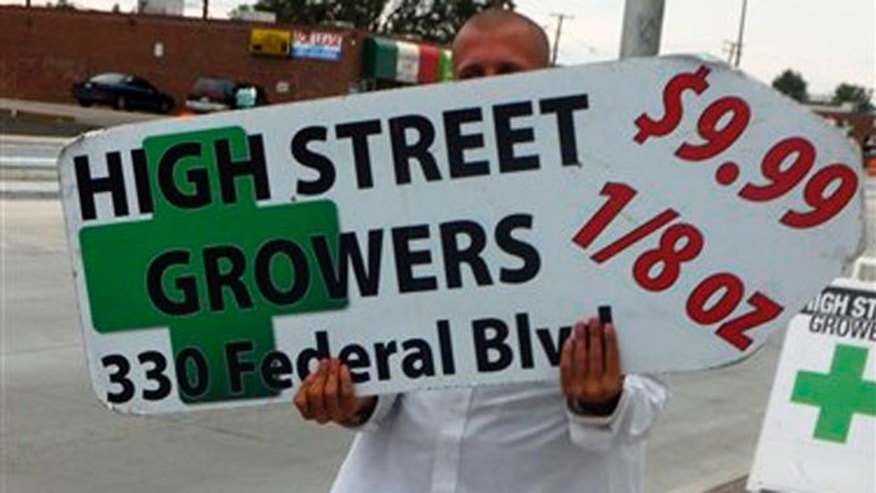 A sign-spinner outside a west Denver medical marijuana dispensary advertises low-cost pot as rush hour drivers pass the pot shop on Monday, Aug. 13, 2012. The spinner, who wouldn't give his name, could be out of a job under an outdoor advertising ban was approved by the Denver City Council.