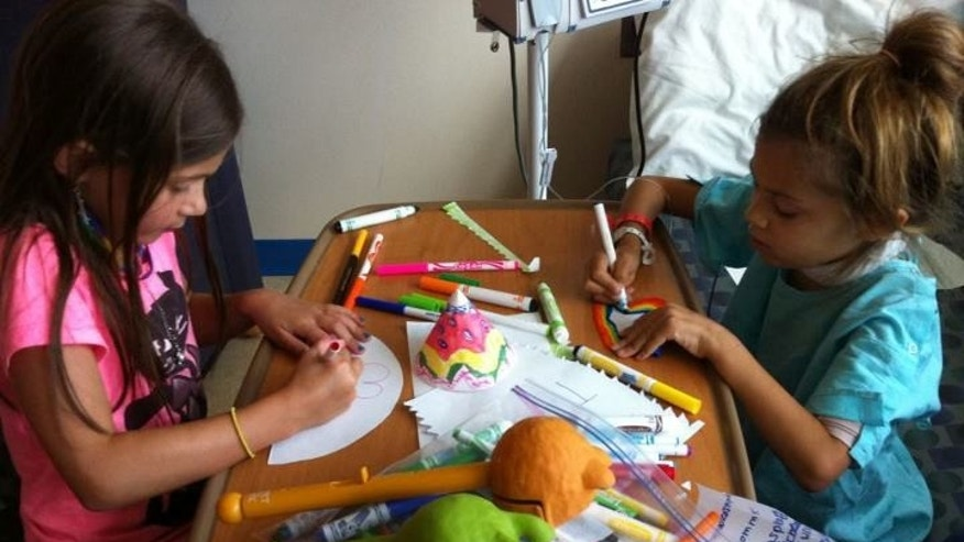 Allie colors at the hospital with her sister Claire. (Courtesy Stephanie Barone)