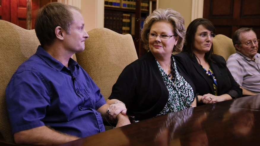 Teresa Russell, second from left, comforts her brother, Jeffrey Russell, left, as Jeffrey talks about their mother, Janet Russell, who is suffering from a deadly fungal meningitis.