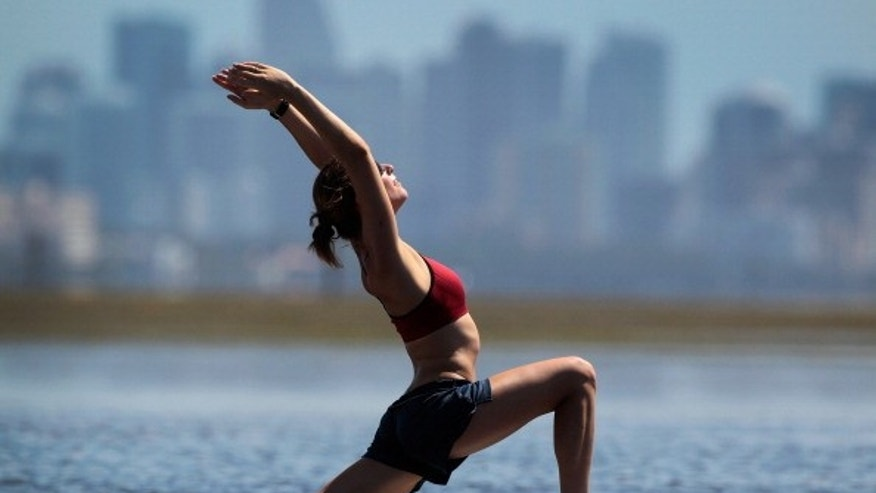 A yoga instructor leads a class using a paddleboard in Miami, Florida.