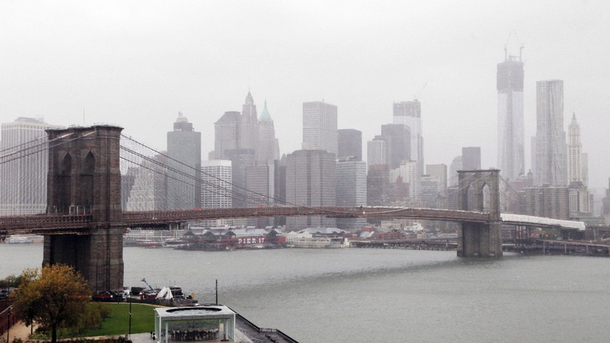 Rain and wind pass over the Brooklyn Bridge and the New York skyline as Hurricane Sandy advances on the city, Monday, Oct. 29, 2012. Hurricane Sandy continued on its path Monday, forcing the shutdown of mass transit, schools and financial markets, sending coastal residents fleeing, and threatening a dangerous mix of high winds and soaking rain.  (AP Photo/Mark Lennihan)