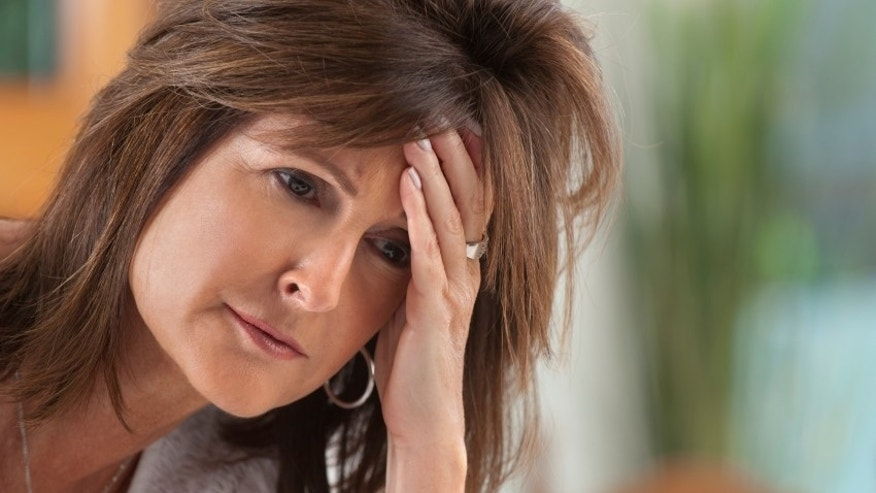 Worried Mature woman holding her head