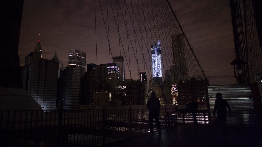 Much of lower Manhattan remains dark, as viewed from the darkened Manhattan side of the pedestrian walkway of the Brooklyn Bridge, Thursday, Nov. 1, 2012 in New York. In the wake of superstorm Sandy, power outages still plague much of the New York area. (AP Photo/Craig Ruttle)