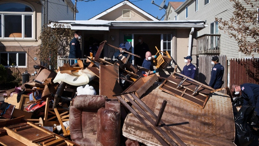 Members of the United States Coast Guard help clear a house in the Midland Beach neighborhood, on Staten Island, N.Y. Nov. 9, 2012. (REUTERS/Andrew Burton)