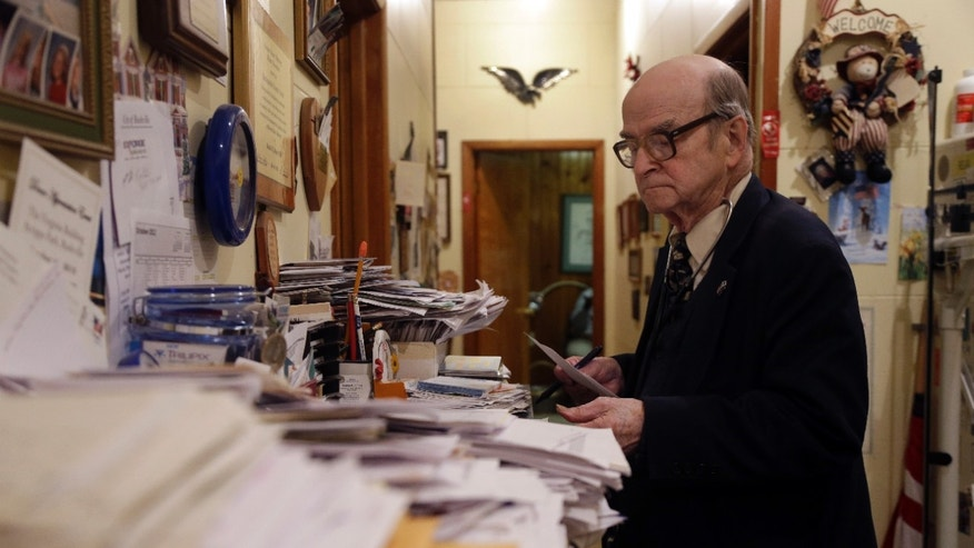 Oct. 30, 2012: Dr. Russell Dohner looks over paper records between seeing patients in Rushville, Ill. (Jeff Roberson/AP)