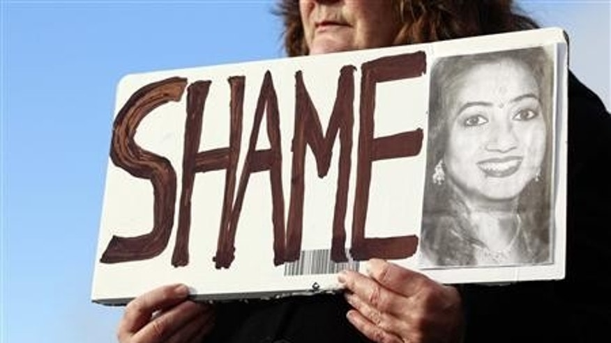 Mary Phelan holds a picture of Savita Halappanavar in protest outside University Hospital Galway in Galway, Ireland.