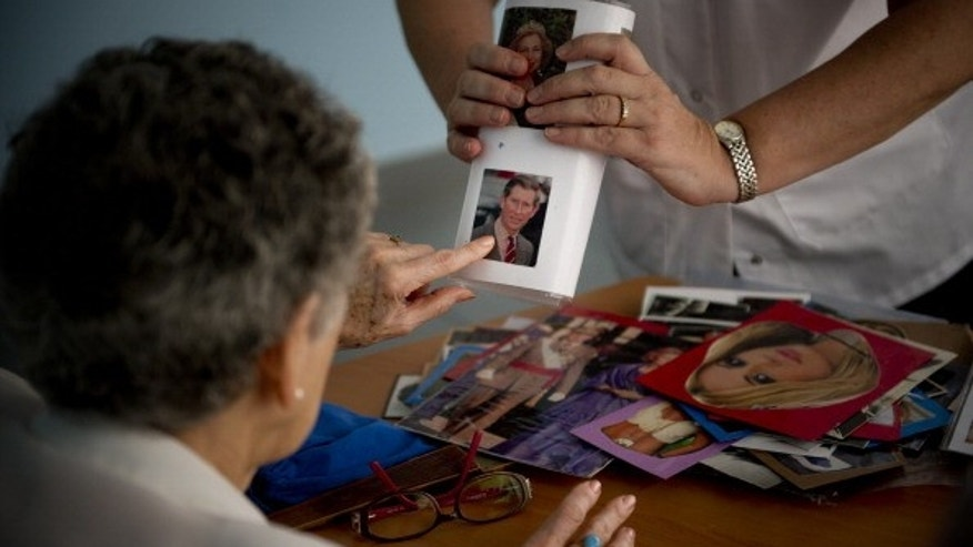 Social worker Nuria Casulleres shows a portrait to an elderly woman during a memory activity in Spain.