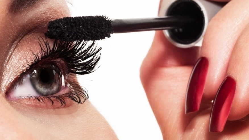 Woman eye with long eyelashes and mascara brush