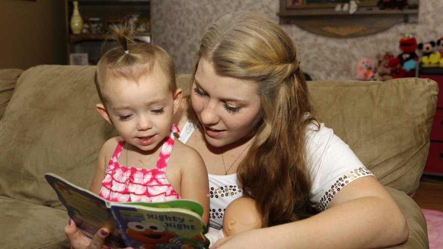 Kali Gonzalez reads to her daughter Kiah, 2, at their home in St. Augustine, Fla.
