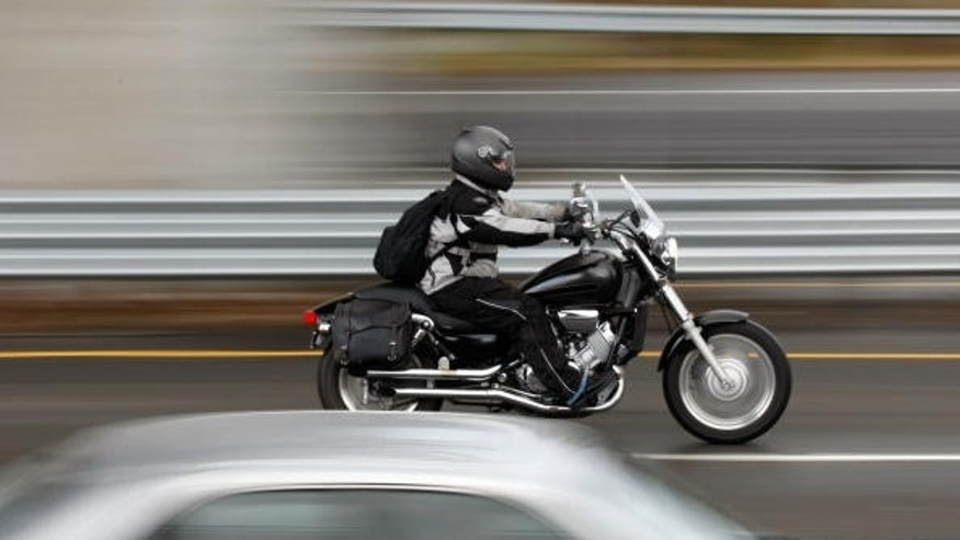 A motorcyclist rides between cars in slow moving traffic on Highway 101 in Corte Madera, California.