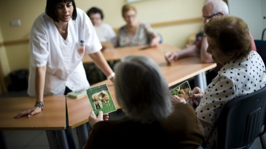 An elderly woman holds a picture of a sheep as she try to remember the name of the animal during a memory activity at the Cuidem La Memoria elderly home, which specializes in Alzheimer patients, in Barcelona, Spain.