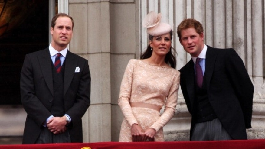 Prince William, Duke of Cambridge, Catherine, Duchess of Cambridge and Price Harry wave to the crowds from Buckingham Palace.