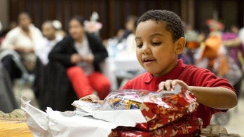 NEW YORK, NY - DECEMBER 25:  Donovan Gonzalez, age six, opens a gift during a Christmas dinner hosted by Engine 277, Ladder 112 of the Fire Department of New York on December 25, 2011 in the Bedford Stuyvesant neighborhood of Brooklyn, New York. Approximately 45 families were invited to the dinner through Housing Bridge, a local organization, and the US Department of Housing Development. The firefighters paid for the event with their own money.  (Photo by Andrew Burton/Getty Images)