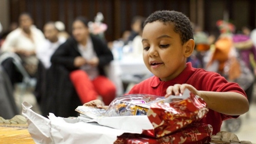 Donovan Gonzalez, age six, opens a gift during a Christmas dinner hosted by Engine 277, Ladder 112 of the Fire Department of New York.