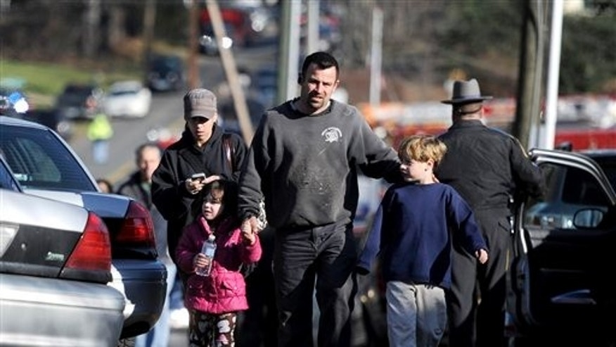 Parents leave a staging area after being reunited with their children following a shooting at the Sandy Hook Elementary School in Newtown, Conn.