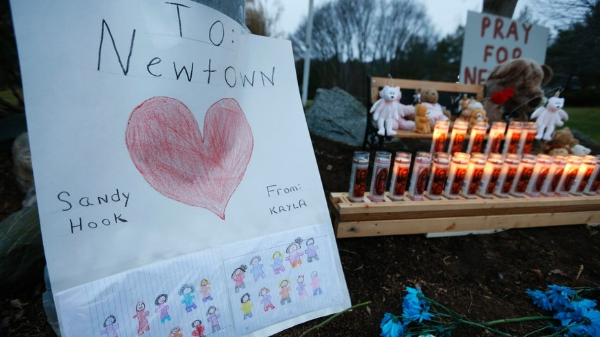 A child's message rests with a memorial for shooting victims in Newtown, Conn.