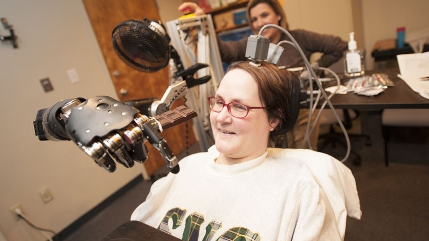 Jan Scheuermann, who has quadriplegia, brings a chocolate bar to her mouth using a robot arm she is guiding with her thoughts. Research assistant Dr. Elke Brown watches in the background. CREDIT: UPMC