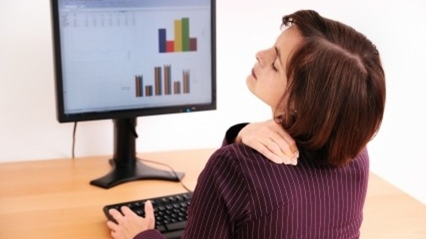 Business woman with neck pain. Focus on hand on neck with blurred monitor on table in background.